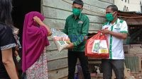 Sudirman Saat mendampingi Iskandar Ketua PKB Bombana menyerahkan bantuan paket sembako