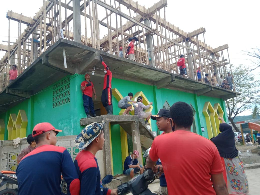 Personil Damkar Bombana terlibat membantu warga gotong royong mengecor lantai II masjid.