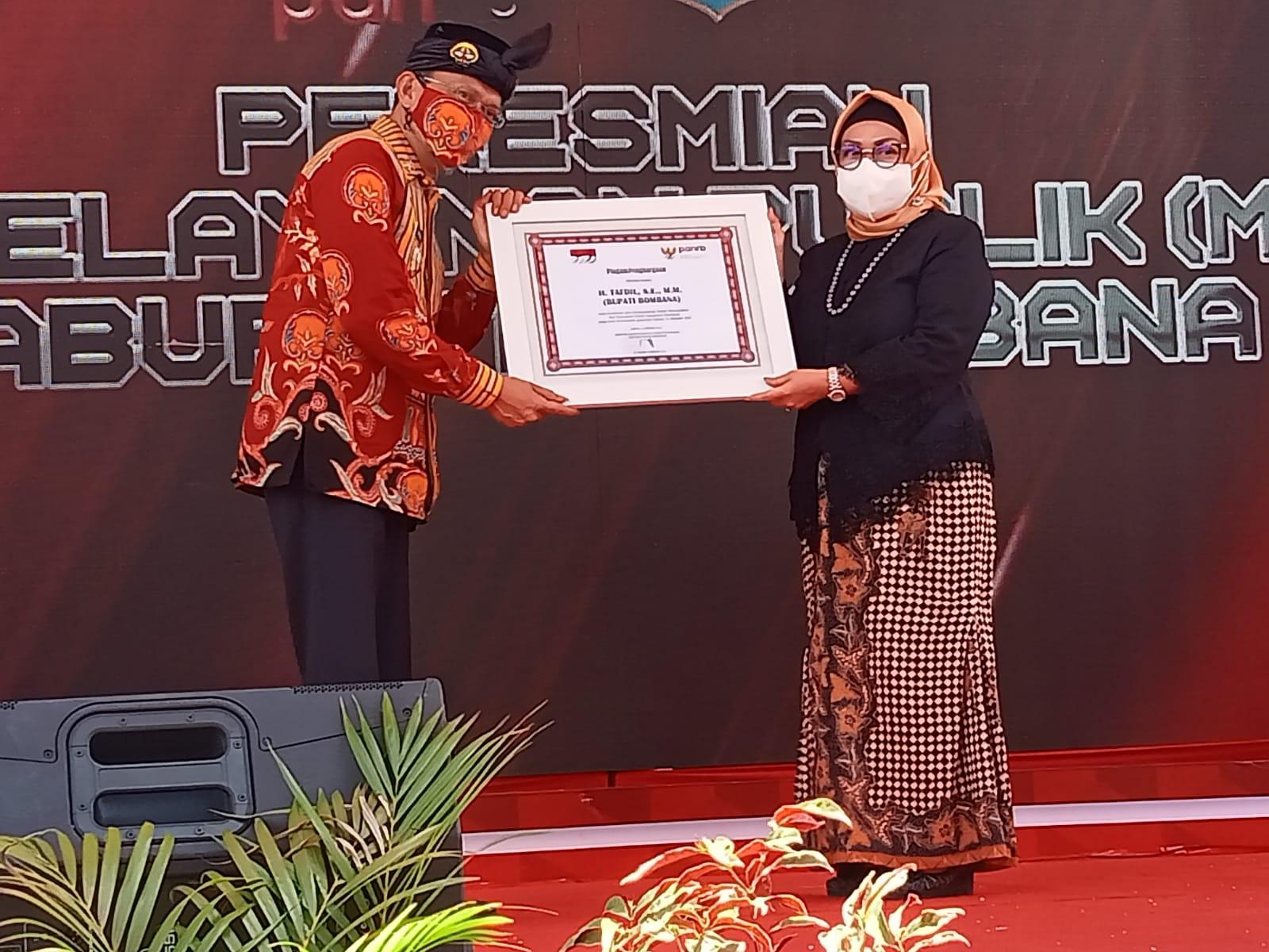 Bupati bombana H. Tafdil (Kiri) saat menerima Piagam dari Deputi Bidang Pelayanan Publik Kemenpan-RB, Diah Natalisa (Kanan)